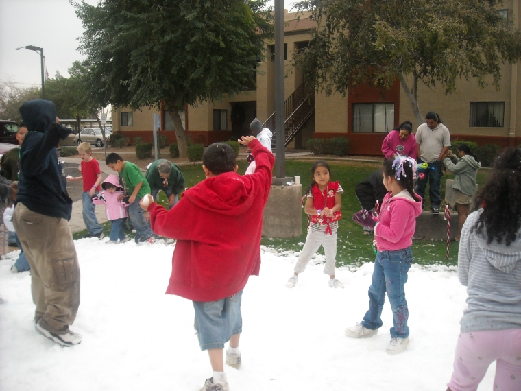 "The children at Villas de Merced played with ""snow,"" a rare sight in Mesa."