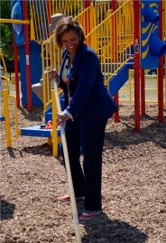 Congresswoman Robin Kelly helps spread mulch on the new playground site. Photo Credit: Daniel Olsen