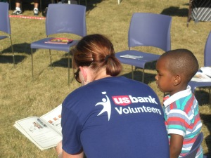 US Bank volunteers read to a student at the Pullman Wheelworks back-to-school celebration event