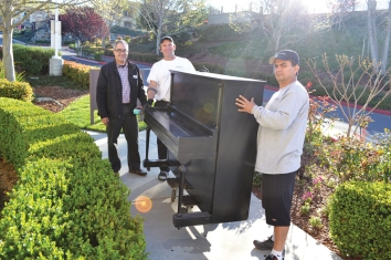 Eddie Zacapa, left, leads the way for Steve Stokes and his employee to deliver a donated piano to White Rock Village's family youth room. A tenant has already offered free lessons to any of the complex's 200 children. All they needed was a piano ... until now. Picture originally captured by: Julie Samrick|Village Life