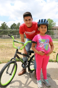 A young man wearing a red shirt with a child wearing a helmet and close to her bike