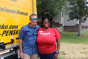 Two people posing for a photograph. On the left, a man in a blue shirt, on the right, a woman in a red shirt.